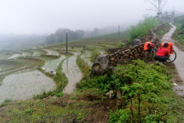 Putting waterproof covers on the bags wit the Sapa paddy fields in the background